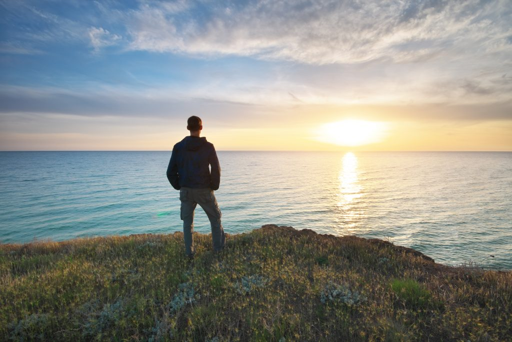 Young man watching the sun and sea